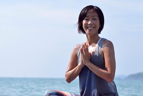 笑顔が素敵なヨガインストラクターの上地紀子さん。「自然のエネルギーを一緒に感じましょう」